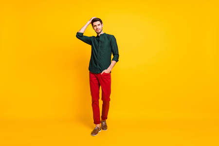 Full length body size photo of masculine attractive man approaching you with hand in pocket touching his hair to show you his hairdress isolated over vivid color background