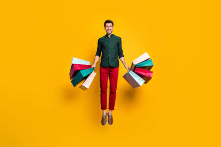 Full length photo of amazed funky crazy guy jump hear wonderful sales scream wow go shop buy purchase hold many bags wear stylish green shirt red pants trousers isolated yellow color background Stock fotó