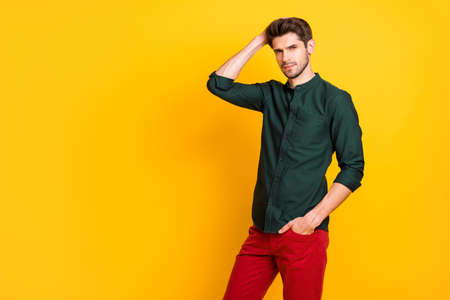 Portrait of gorgeous man rich wealthy businessman attract girls touch his hair after anti dander effect shampoo form hairdresser wear green shirt red pants trousers isolated yellow color background