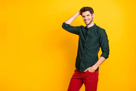 Photo of positive attractive man adjusting his hair with hand in pocket smiling toothily pleased satisfied with the result of barber work isolated bright color background