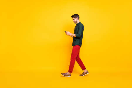 Full length body size photo of moving cheerful walking addicted attractive man browsing through his telephone wearing red pants trousers footwear isolated over yellow vivid color background