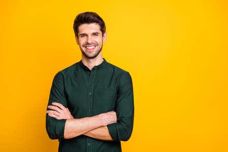 Portret van zelfverzekerde coole ondernemer die zijn handen kruist, ziet er positief uit, vrolijke emoties, echte professionele expert draagt casual kleding geïsoleerd over gele kleurachtergrond Stockfoto