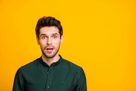 Photo of fearful man seeing terrible things occurring with negative stressful emotions on face in green shirt isolated vivid color background