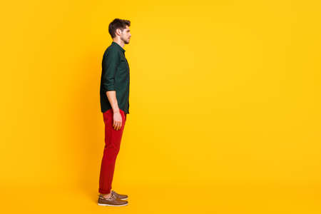 Full length body size photo of candid pensive indifferent man standing straight side profile looking into empty space isolated over bright color background
