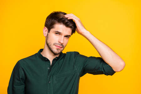Close up photo of virile confident man touching his hair worried about its falling off isolated over vivid color yellow background