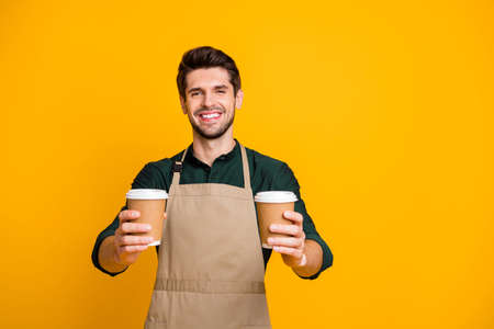 Portrait of positive cheerful guy worker in coffee bar shop hold paper card cup offer to his client mug with hot cappuccino wear apron green shirt isolated over yellow color background