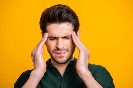 Close up photo of suffering man in pain with bristle shutting his eyes in a fit of hurtful illness isolated over yellow vibrant color background