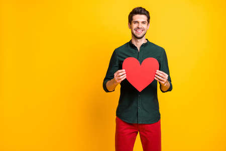 Portrait of positive happy cheerful guy hold big red papercard heart want give his girlfriend for 14-february 8-march date weekends wear casual style clothing isolated over yellow color background