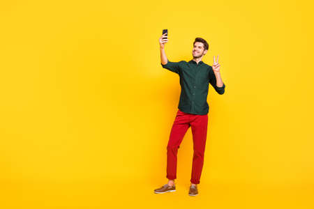 Full body photo of positive cheerful guy have fun spring holidays tale selfie on his smartphone make v-signs greet blog followers wear casual style outfit sneakers isolated yellow color background Stok Fotoğraf