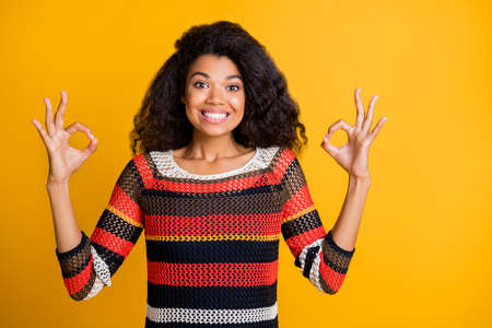 Close-up portrait of nice attractive girlish cheerful cheery wavy-haired girl in knitted sweater showing double ok-sign isolated on bright vivid shine vibrant yellow color background