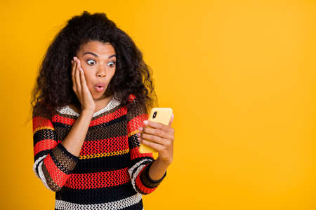 Portrait of astonished impressed afro american girl use her cellphone read feedback feed news on social network copyspace stare stupor wear striped jumper isolated over yellow color background Фото со стока