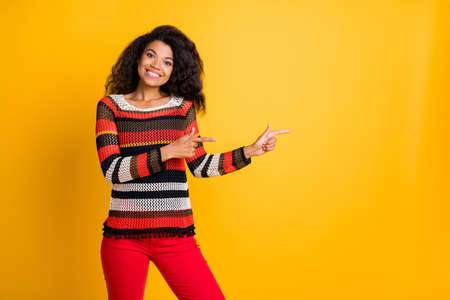 Look discounts. Portrait of confident promoter afro american girl feel positive emotions point finger copyspace direct tips wear modern jumper red pants trousers isolated yellow color background Stock Photo