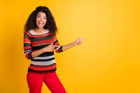 Portrait of her she nice attractive cheerful glad wavy-haired girl in knitted sweater pointing aside advice ad solution follow subscribe isolated on bright vivid shine vibrant yellow color background 版權商用圖片