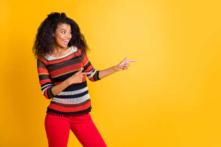 Portrait of her she nice attractive lovely cheerful glad wavy-haired girl in knitted sweater pointing aside solution follow subscribe isolated on bright vivid shine vibrant yellow color background