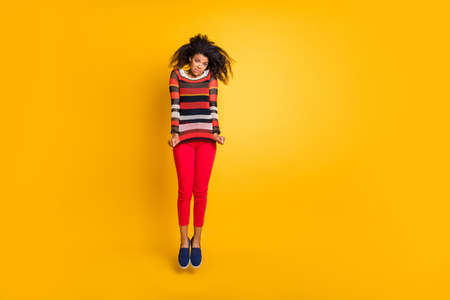 Full size photo of disappointed brunette curly hair girl jump dont like her big size disgusting sweater bite lips wear striped trendy pullover red stylish pants isolated over yellow color background Banco de Imagens