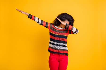 Profile side photo of dreamy serious girl hip-hop lover dab dancer hide face hands raise wear striped shirt trousers isolated over shiny color background