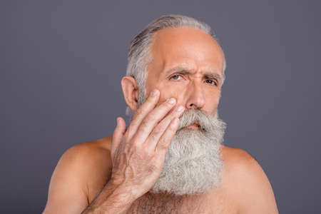 Photo of worried old mature male touching his cheek with pimple on it smoothing wrinkles out on his face isolated grey color background