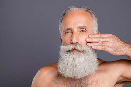 Close up photo of aged handsome man metrosexual touching facial skin applying anti age cream gel amazing neat long beard shirtless isolated grey background