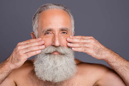 Close up photo of old mature man pulling smoothing his wrinkles out under his eyes isolated over grey color background Reklamní fotografie