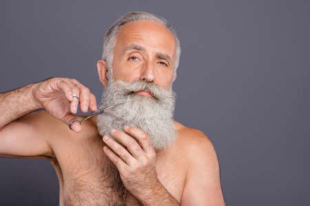 Close up photo of mature grandfather grey old man cutting his beard away, standing naked isolated over gray background Stock fotó