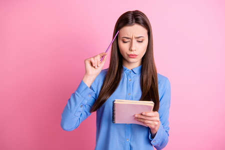 Photo of pensive confused interested student solving task given staring at notepad misunderstanding with confused facial expression wearing blue shirt isolated pink pastel color background