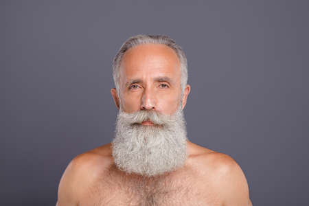 Photo of serious confident naked old man staring into camera being shirtless waiting for clothing to be given back to him isolated over grey color background