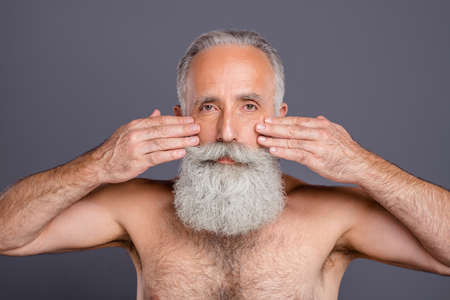 Portrait of old mature handsome grandfather worried about wrinkles appearing on his face isolated naked over grey color background