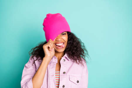 Photo of cheerful impolite rude girl sticking her tongue out in striped t-shirt jacket pink showing pulling her cap upon her head isolated vivid teal color background Reklamní fotografie
