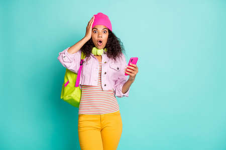 Photo of speechless shocked stunned crazy girl having received feedback from her followers on social media wearing cap headwear striped t-shirt yellow pants isolated pastel teal color background