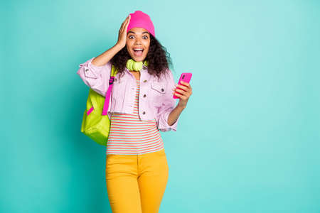 Photo of cheerful positive pretty nice cute girl in yellow pants jacket pink t-shirt with amazement on face holding telephone fashionable model isolated teal color pastel background Stock Photo