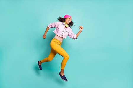 Turned full length body size photo of casual positive running jumping girl aspiring for discounted goods wearing yellow pants trousers pink jacket striped t-shirt isolated teal color background vivid