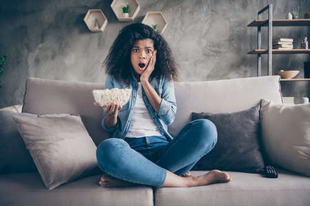Photo of pretty dark skin wavy lady homey mood eating popcorn watching television horror show hand on cheek sitting cozy couch casual jeans outfit flat indoors