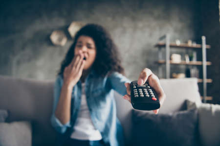 Photo of dark skin wavy lady homey mood holding tv remote control sleepy boredom yawning turn television off sitting comfy couch casual denim outfit flat indoors blurry focus