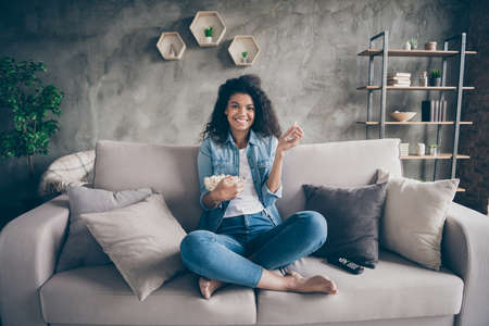 Photo of pretty dark skin wavy lady homey mood eating popcorn watching favorite humor television show sitting cozy couch casual jeans outfit flat indoors
