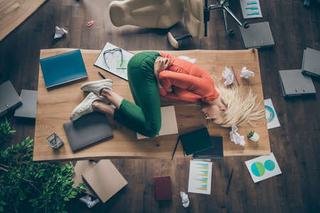High angle above view photo of corporate messy atmosphere unorganized blond business lady lying table suffering period pms holding hurt belly wear casual outfit indoors