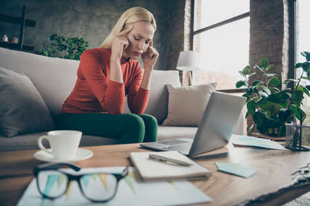 Photo of blond business lady tired hard-working holding temples suffering terrible migraine wear specs orange pullover sitting sofa table notebook diary coffee indoors Reklamní fotografie