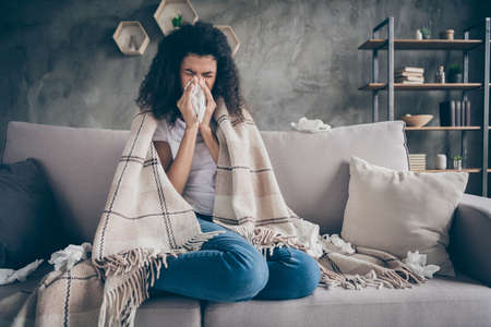 Photo of unhealthy dark skin wavy lady suffering flu caught cold sneezing paper napkins everywhere sitting couch covered plaid blanket living room indoors