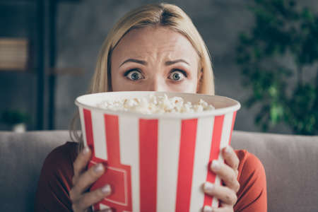 Closeup photo of pretty funny lady eating popcorn watching television horror film eyes full of fear hiding face afraid sitting couch casual outfit flat living room indoors Stock Photo