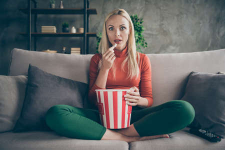 Photo of pretty funny lady homey mood eating popcorn watching television horror show eyes full of fear sitting comfort couch casual outfit flat living room indoors