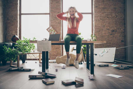 Full length photo of mad busy freelancer secretary with negative mood made mistake fired sit on table feel overworked yell touch blonde hair in messy office workstation loft