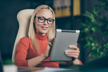 Perfect leader big company owner charming woman sit chair table use tablet search modern start-up development news employee training in office loft wear red turtleneck