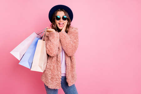 Photo de jolie dame tenir transporter de nombreux packs shopper tourisme à l'étranger regarder des prix de vente incroyables la main sur la joue magasin porter veste soleil specs chapeau jeans isolé fond rose