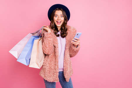 Photo of beautiful millennial model lady tourist hold many packs telephone reading good comments mall wear stylish fluffy jacket retro blue hat jeans isolated pink background