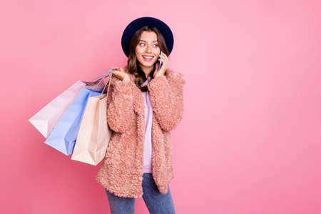 I love Paris shopping. Photo of beautiful millennial model lady tourist hold packs store telephone speak with parents wear stylish fluffy jacket retro hat jeans isolated pink background