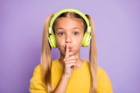 Close up photo of astonished kid use headset listen music find melody in playlist show index finger dont tell confidential information wear pullover isolated purple color background Banco de Imagens
