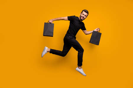 Full body profile photo of handsome guy jumping high running shopping store buying clothes hold many bags wear black t-shirt pants isolated yellow color background