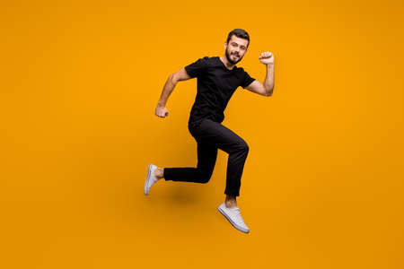 Full length profile photo of handsome millennial guy jumping high rush shopping mall black friday offers season wear black t-shirt pants isolated yellow color background