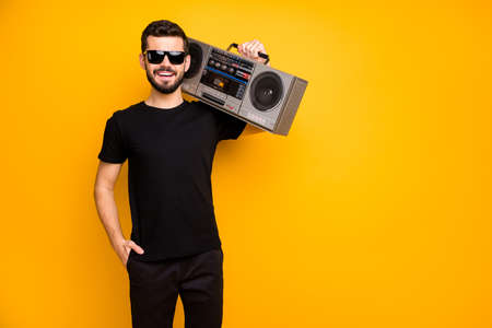 Portrait of cool charming positive guy hold boom box on his shoulder want listen vintage music on journey wear black friday clothes isolated over bright color background