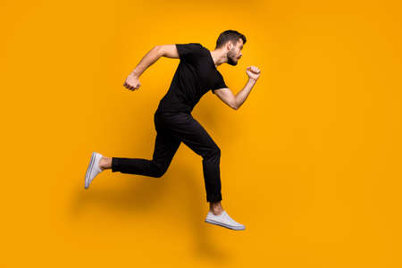 Full length profile photo of handsome millennial guy jumping high rushing low prices discount shopping wear black t-shirt trousers isolated yellow color background