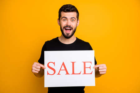Photo of handsome millennial guy offer low prices shopping showing holding white paper card sale announce wear black t-shirt isolated yellow color background